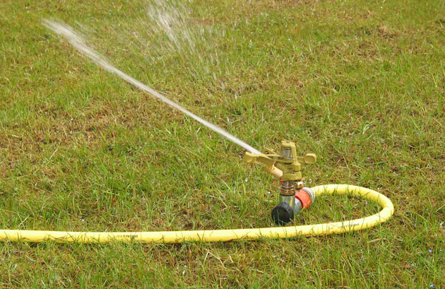 copper lawn sprinkler spraying water